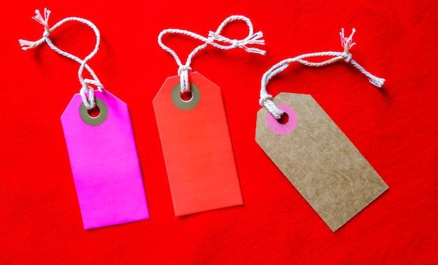 Trois balises colorées sur une corde blanche, fond rouge.