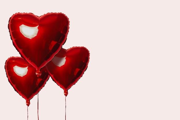 Trois ballons à air rouge en forme de coeur sur une surface légère