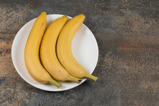 Trois bananes mûres sur plaque blanche.