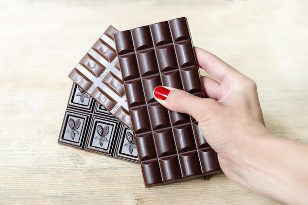 Trois barres de chocolat de différents types dans une main féminine