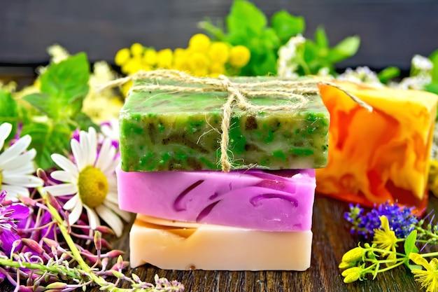 Trois barres multicolores de savon fait maison, fleurs d'épilobe, tanaisie, camomille, trèfle, achillée millefeuille, tutsan et reine des prés, feuilles de menthe et de mélisse sur fond de planches de bois