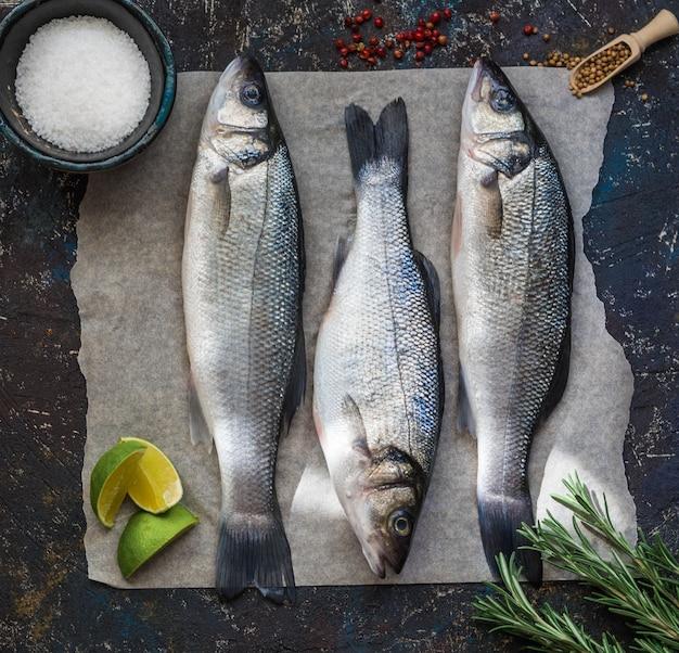 Trois bars de poisson cru et autres ingrédients sur vintage noir. vue de dessus