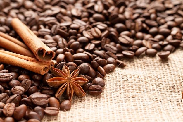 Trois bâtons de cannelle parfumée naturelle indiquent un astérisque d'anis ou de badiane sur des grains de café.