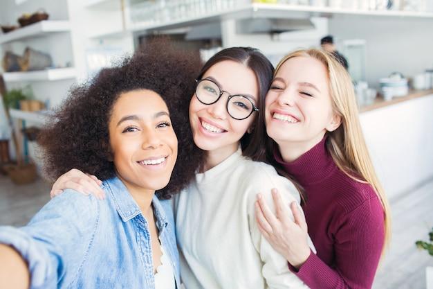 Trois beaux amis prennent selfie ensemble. il y a une fille afro-américaine, une brune et une blonde. ils regardent et sourient. les filles sont très gaies.