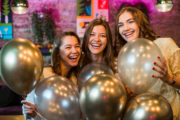 Trois beaux amis souriants tenant des ballons d'argent profitant en fête