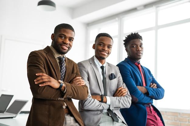 Trois beaux jeunes hommes africains en costumes