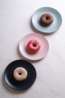 Trois beignets en ligne sur des assiettes, beignets au chocolat, rose et vanille avec paillettes