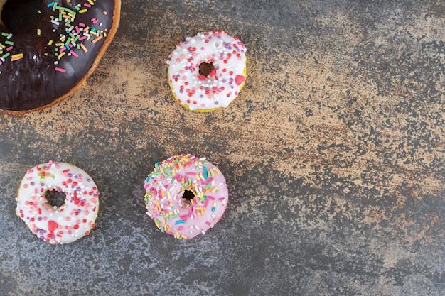 Trois beignets de la taille d'une bouchée à côté d'un gros beignet sur une surface en bois