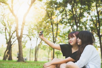 Trois belles amies étant modernes en prenant des selfies.