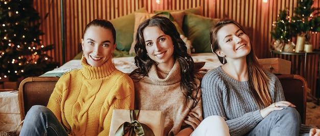 Trois belles amies joyeuses et heureuses de jeunes filles donnent des cadeaux de noël sur le fond d'un arbre du nouvel an à la maison