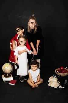 Trois belles écolières de différentes classes et pré-école garçon sur fond noir