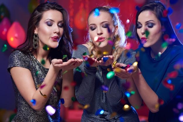 Trois belles femmes parmi les confettis