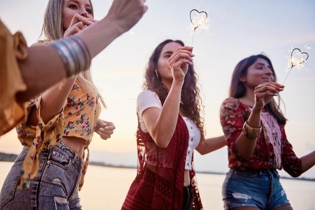 Trois belles femmes s'amusant avec des cierges magiques sur la plage