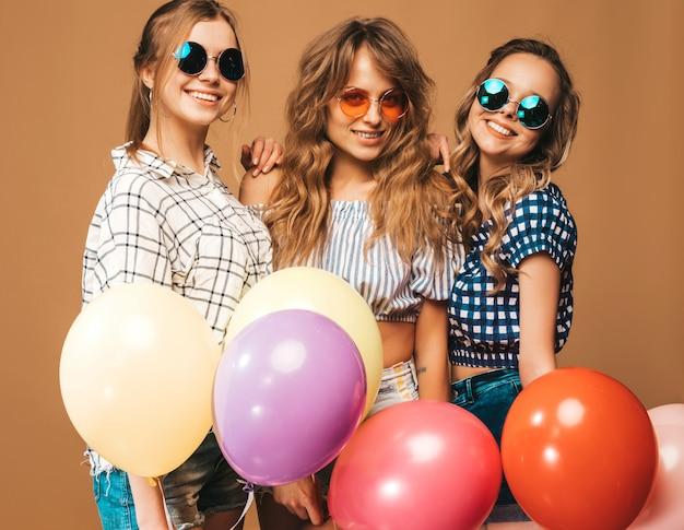 Trois belles femmes souriantes en chemise d'été à carreaux et des lunettes de soleil. filles posant. modèles avec des ballons colorés. s'amuser, prêt pour l'anniversaire de célébration