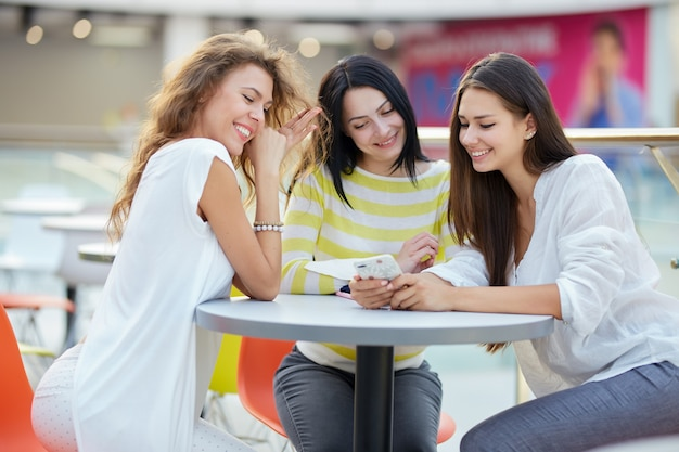 Trois belles filles élégantes sont assises à une table dans un café du centre commercial moderne et discutent après le shopping.