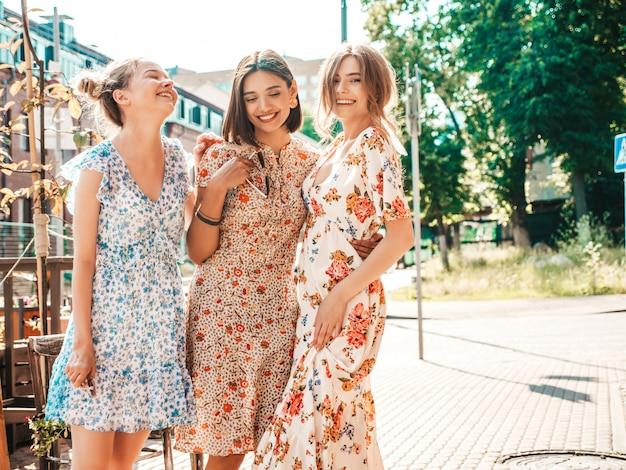 Trois belles filles souriantes en robe d'été à la mode posant dans la rue