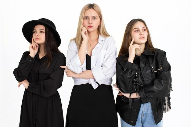 Trois belles jeunes filles envisagent de résoudre le problème. photo sur fond blanc