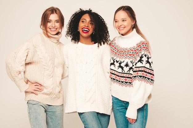 Trois belles jeunes filles hipster souriantes dans des pulls d'hiver à la mode. modèles positifs s'amusant et s'embrassant