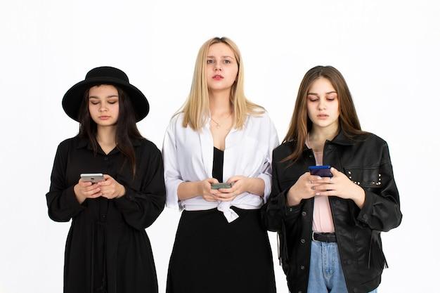 Trois belles jeunes filles regardent leurs smartphones. photo sur fond blanc