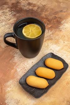 Trois biscuits et thé dans une tasse noire sur table de couleurs mélangées