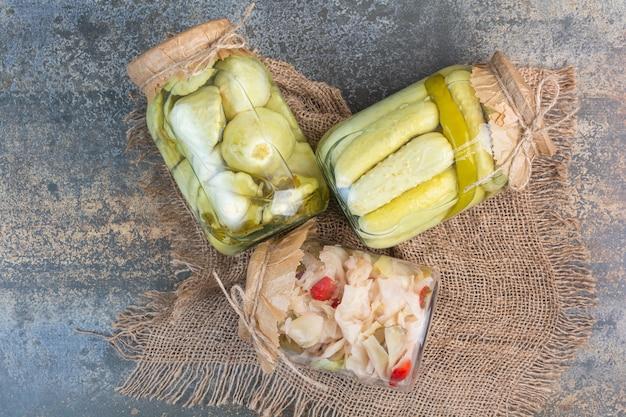 Trois bocaux divers légumes confits sur une toile de jute.