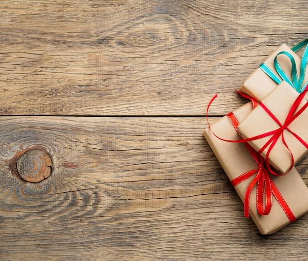 Trois boîtes-cadeaux de papier kraft sur fond en bois