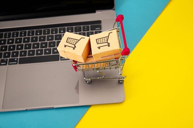 Trois boîtes en papier dans un petit panier sur un clavier d'ordinateur portable. concept d'achat et de livraison en ligne.