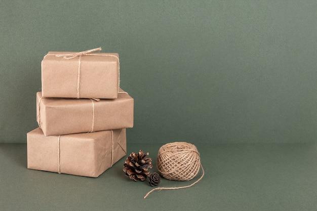 Trois boîtes en papier kraft, ficelle et cônes sur fond vert. concept vacances de noël ou du nouvel an, zéro déchet joyeux noël. vue de face espace de copie.