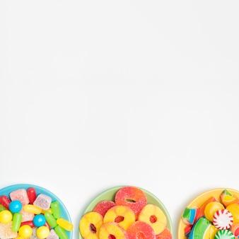 Trois bol sur la table avec des bonbons et des fruits