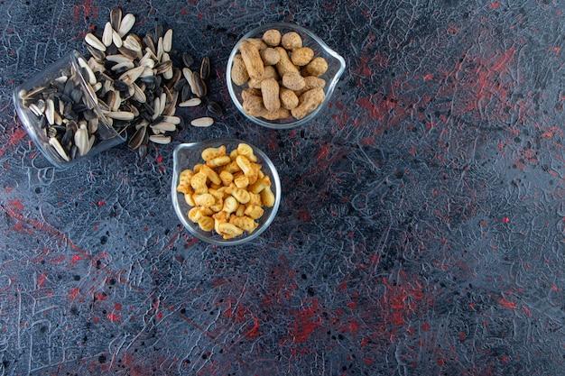 Trois bols de cacahuètes, graines de tournesol et craquelins sur fond bleu.