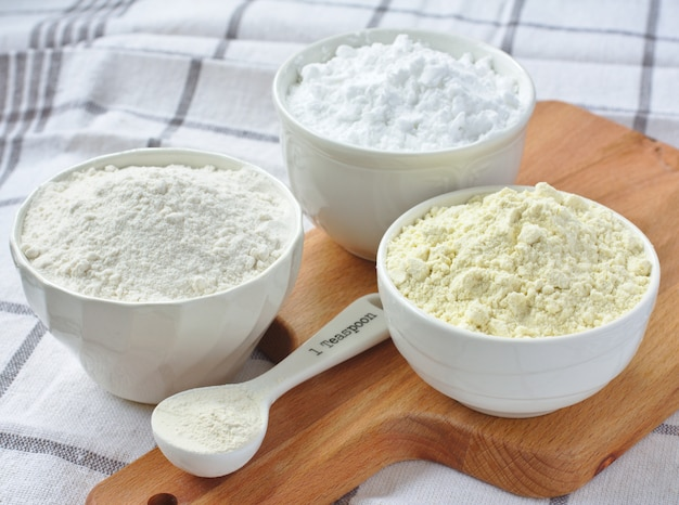 Trois bols avec de la farine sans gluten - farine de riz, farine de millet et fécule de pomme de terre et cuillère avec gomme xanthane