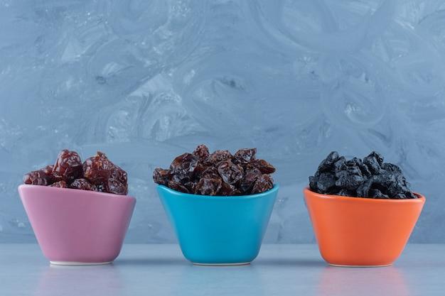 Trois bols de fruits secs , sur la table en marbre.