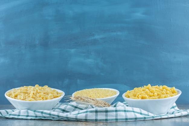Trois bols de pâtes à côté de deux blés sur la serviette, sur la surface en marbre.