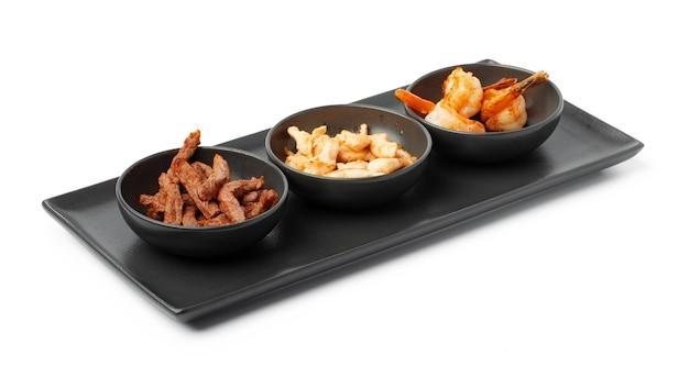 Trois bols avec des tranches de poulet de boeuf cuites et des crevettes isolées sur blanc