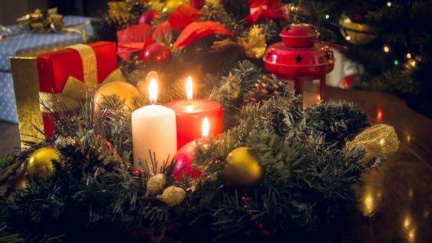 Trois bougies allumées sur une couronne de l'avent au salon