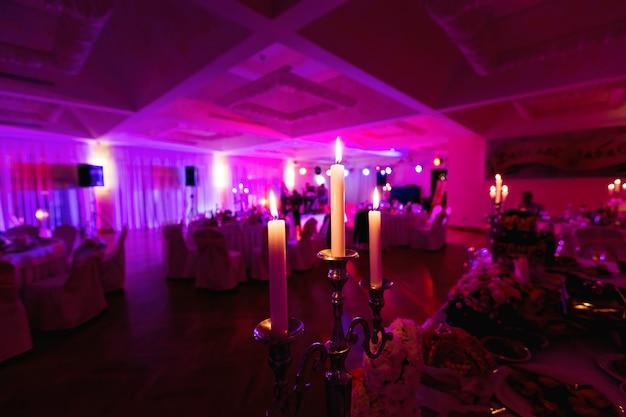 Trois bougies d'éclairage dans un restaurant de luxe sur une table de mariage