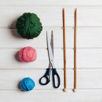 Trois boules de laine, des ciseaux et des aiguilles
