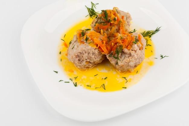Trois boulettes de viande sur une assiette blanche avec un brin d'aneth