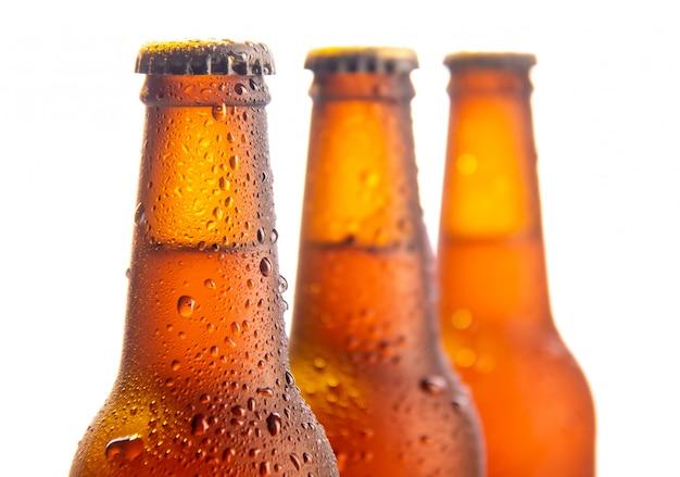 Trois bouteilles de bière fraîche sur blanc