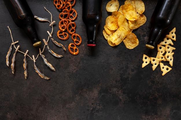 Trois Bouteilles De Bière Avec Frites, Craquelins Salés, Bretzels Et Poisson Séché Photo Premium