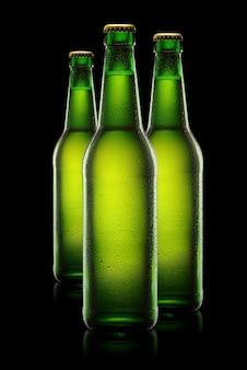 Trois bouteilles de bière humides vertes sur fond noir