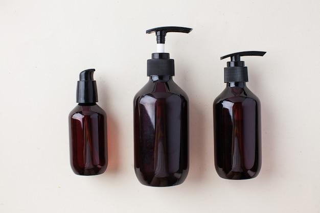 Trois bouteilles brunes différentes avec des produits cosmétiques biologiques naturels zéro déchet naturel