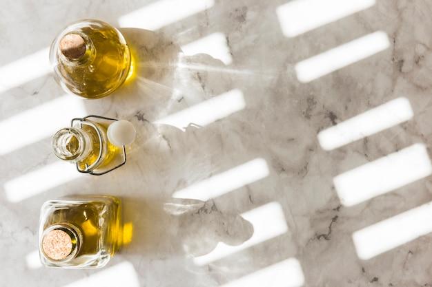 Trois bouteilles d'huile d'olive vierge et saine sous la lumière naturelle du soleil