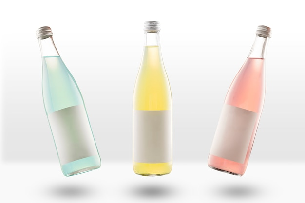 Trois bouteilles en verre de limonade et de boissons gazeuses, avec des étiquettes de maquette vides. jaune, rose et vert clair. vide pour les concepteurs