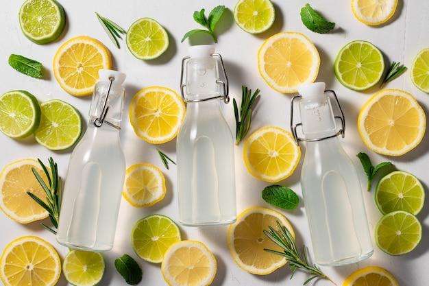 Trois bouteilles en verre de limonade sur fond d'agrumes tropicaux lumineux boisson d'été