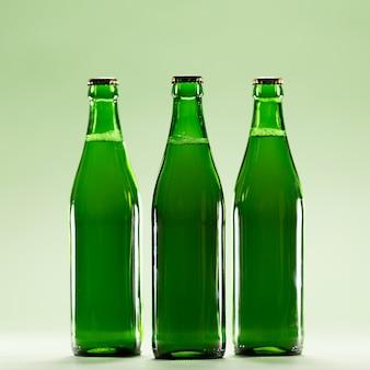 Trois bouteilles vertes sur un fond vert clair.