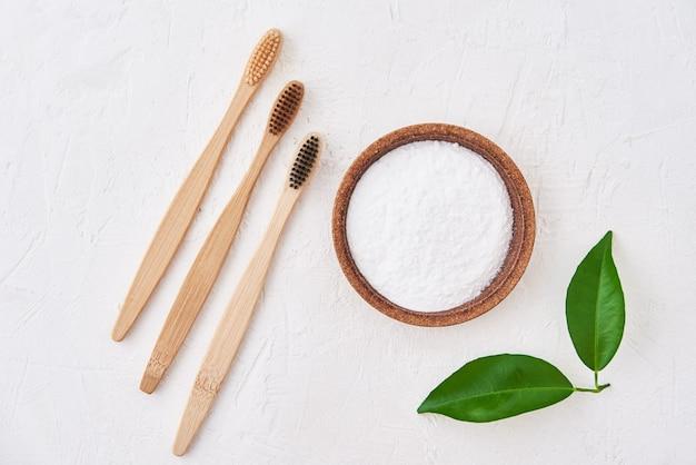 Trois brosses à dents en bambou en bois et bicarbonate de soude, vue du dessus. brosses à dents écologiques, concept zéro déchet