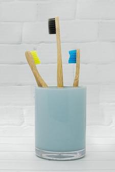 Trois brosses à dents en bois de bambou avec des poils multicolores dans un verre bleu sur fond de mur de briques blanches.