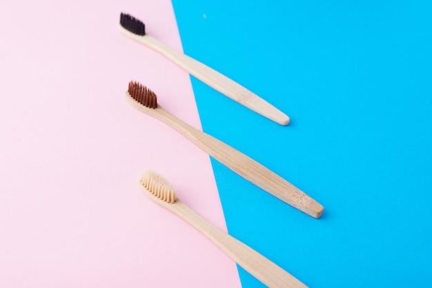 Trois brosses à dents en bois naturel sur un fond de couleur bleu et rose, vue de dessus à plat. concept de zéro déchet et de soins dentaires