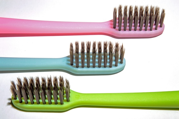 Trois brosses à dents multicolores sur fond blanc.